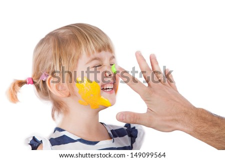 Small girl with paint on her cheek and nose and father's hand