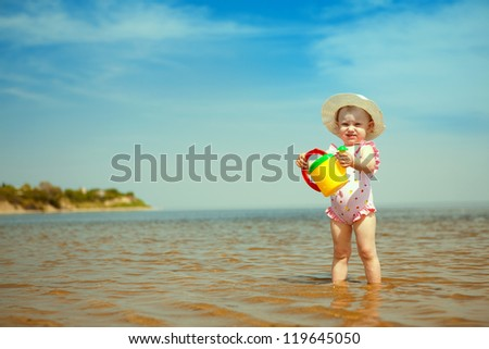 small girl with watering-pot on the seashore - stock photo