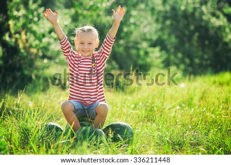 Small girl with watermelons on lawn