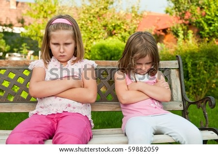 Small girls (sisters) siting on bench offended after quarrel - outdoors in backyard - stock photo