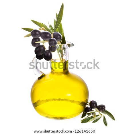 small glass bottle with olive oil, decorated with a small twig with black olives, fruit, isolated on white background - stock photo