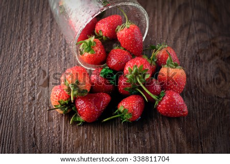 Small glass bowl filled with succulent juicy fresh ripe red strawberries on an old wooden textured table top - stock photo