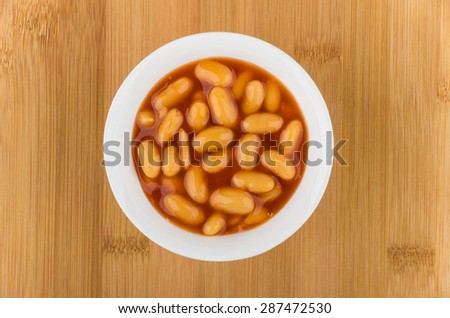Small glass bowl with beans in tomato sauce on wooden board, top view - stock photo