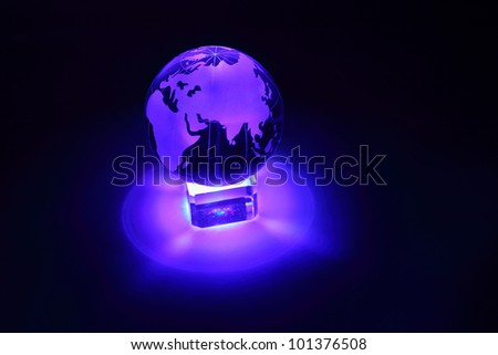 Small glass globe at glass stand is illuminated by blue light from below; Africa and Eurasia - stock photo