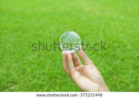 Small glass globe in the hands of men - stock photo