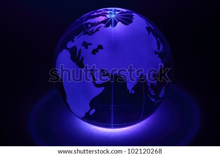 Small glass globe is illuminated by blue light from below; Africa and Eurasia - stock photo