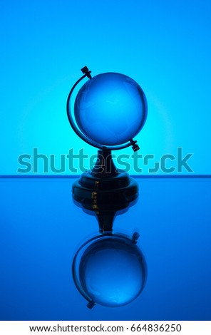 Small glass globe stands on a blue background