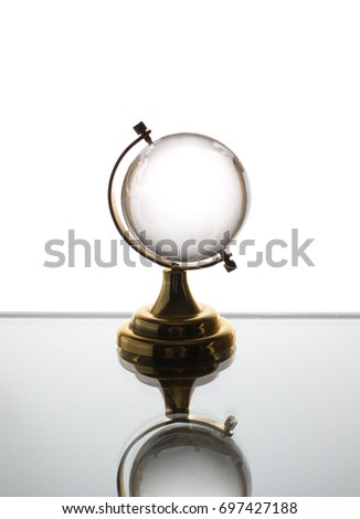 Small glass globe stands on a  white background