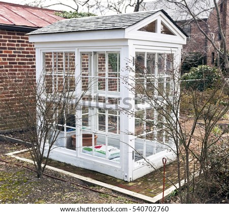 Small glass greenhouse. Early spring. Late winter.