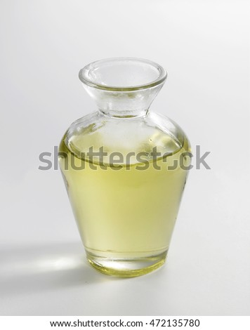 small glass jar of oil on the white background