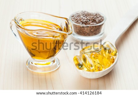 Small glass jug of flax oil, bowl with flax seeds and wooden spoon with fish oil capsules. Sources of Omega-3 for healthy hair, skin and nails.  - stock photo