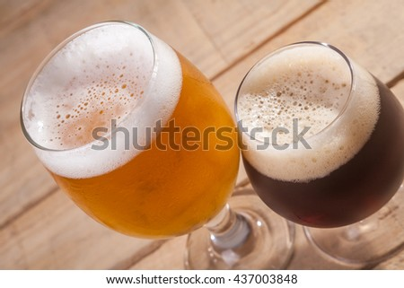 Small glass of dark beer and larger glass of light beer on a wooden table - stock photo