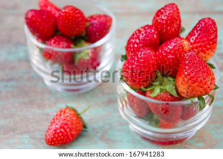 Small glass with succulent juicy fresh ripe red strawberries on wooden textured table top