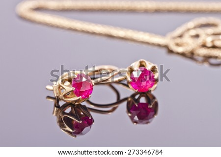 Small gold earrings with semi-precious stones ruby color - stock photo