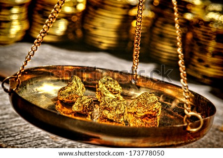 Small gold nuggets being checked for weight old style in an antique measuring scale suspended brass pan at a vintage precious metal dealer shop - stock photo