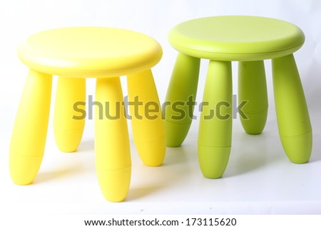 Small green and yellow plastic stool for kids isolated on white - stock photo