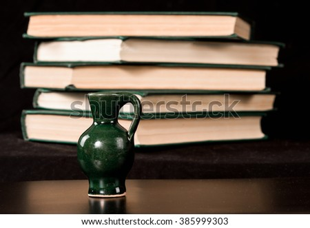Small green ceramic jugs on the background of old books .