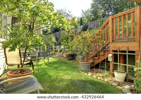 Small green fenced back yard with garden and shed - stock photo