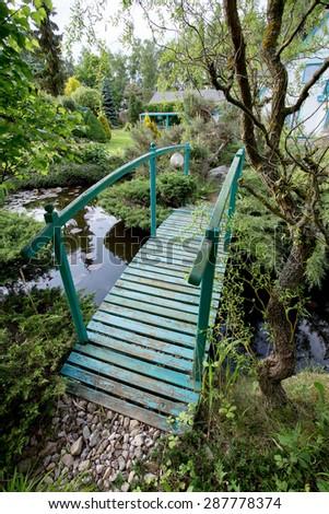 small green footbridge over a pond on spring garden - stock photo