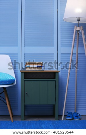 Small Green Table With Books And Lamp Near Blue Wooden Wardrobe