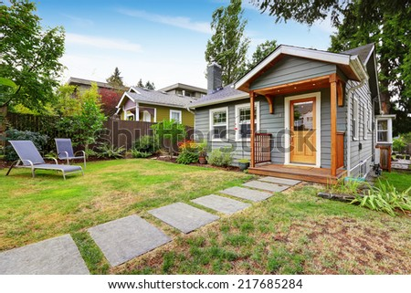 Small grey house with wooden deck. Front yard with deck chairs and flower bed