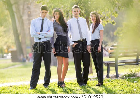 Small group of business people, elegantly dressed, standing in the park,enjoying the sunny day, looking at the camera. - stock photo