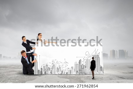 Small group of business people holding banner with construction project - stock photo