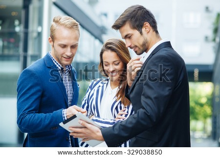 Small group of business people looking at digital tablet and talking outdoors. Selective focus on woman face. - stock photo