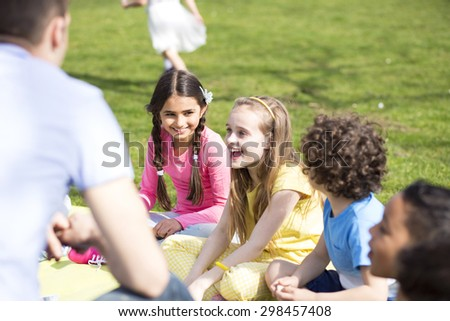 Small group of children sitting on the grass having a lesson outdoors. Only side of the teacher can be seen. The children look to be listening and enjoying themselves.  - stock photo