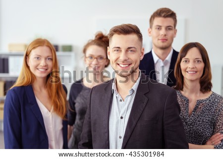 Small group of coworkers in business attire stand closely and smile at the camera - stock photo