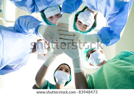Small group of doctor team joining hands,ant's eyes angle view.