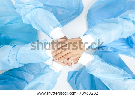 Small group of doctor team joining hands, bird's eyes angle view. - stock photo