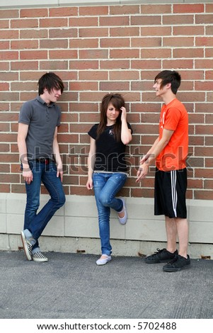 small group of female and male teens ouside of school