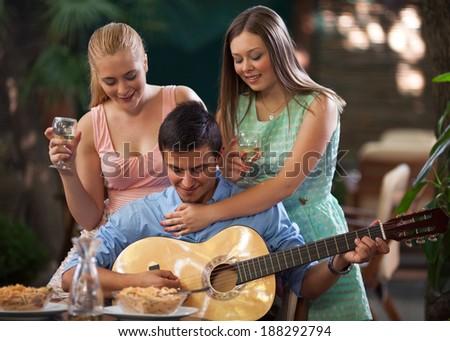Small group of friends enjoying dinner and music together in a restaurant. - stock photo