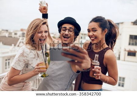 Small group of friends taking selfie on a mobile phone. Young man and women with drinks making funny face while taking a self portrait on smart phone. Having fun on rooftop party. - stock photo