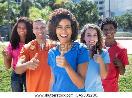 Small group of happy young man and woman showing thumb up