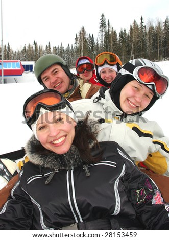 Small group of  snowboarders laying on slope, smiling.
