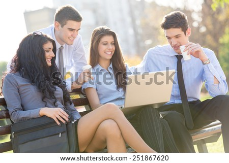 Small group of young business people sitting on a park bench during a break looking at the laptop. - stock photo