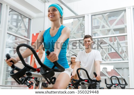 Small group of young people exercising on bikes in fitness center - stock photo
