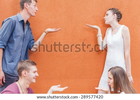 Small group of young people sending a blow kiss to each other. They standing near the red wall background. Celebrate a holiday of International, World Kissing Day 6 July or Valentine's Day, copy space - stock photo