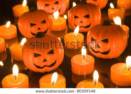 Small Halloween toy Pumpkins surrounded by orange tealight candles