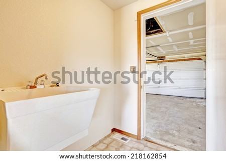 Small hallway with sink and exit to garage - stock photo