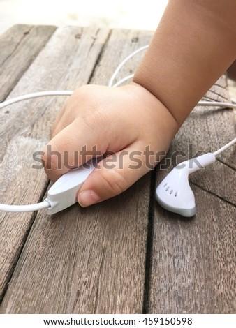 small handle earphones on wood background - stock photo