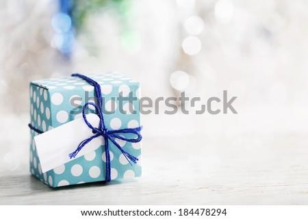 Small handmade gift box over shiny ornaments - stock photo