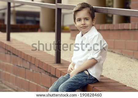 Small  happy boy sitting on the stone wall - stock photo