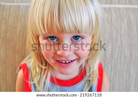 Small happy boy with a long blond hair - stock photo