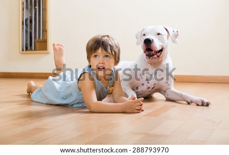 small happy girl on the floor with dogo Argentino  - stock photo