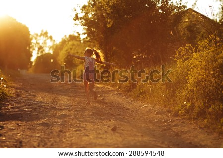 Small happy little girl running along a country road - stock photo