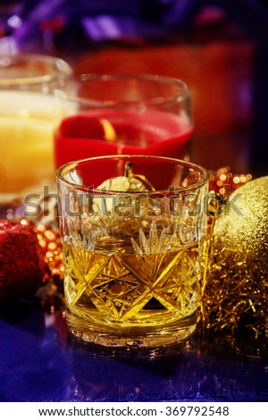 small happy moment of Christmas or New Year`s Eve,a glass of whiskey surrounded by Christmas decoration,toys gifts. - stock photo