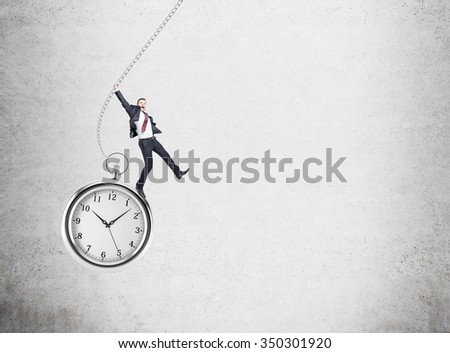 small happy young businessman swinging on huge pocket watch. Concrete wall at the background. Concept of playing with time - stock photo